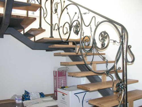 Кованые перила вокруг пространства лестницы выполнены в едином для всей конструкции стиле